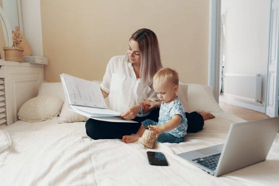 modern mom working at home on laptop with phone while baby plays